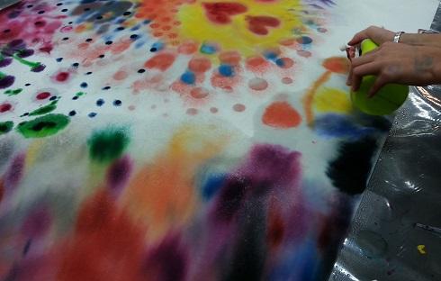 taideterapeuttinen värikäs maalattu kuva johon kuvassa lisätään suihkepullolla vettä