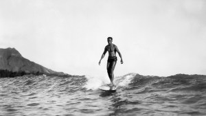 Duke Kahanamoku surfing with Diamond Head at left in the background on Oahu Island in the Hawaiian Islands.