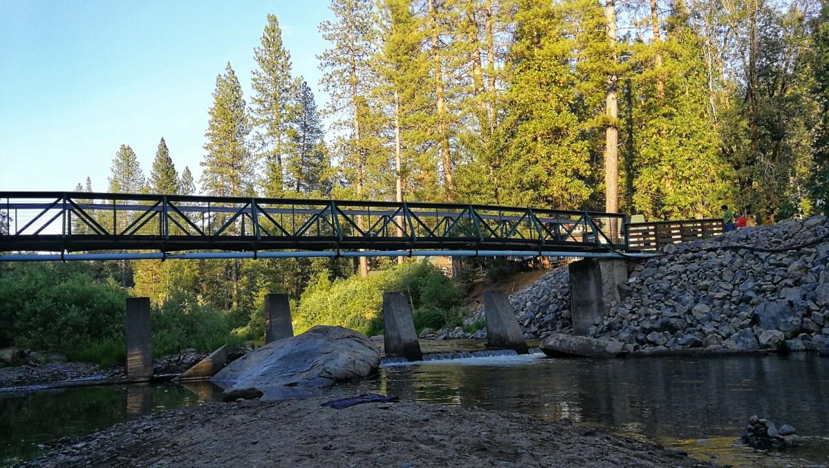 Holzbrücke führt über den Fluss durch den Campingplatz