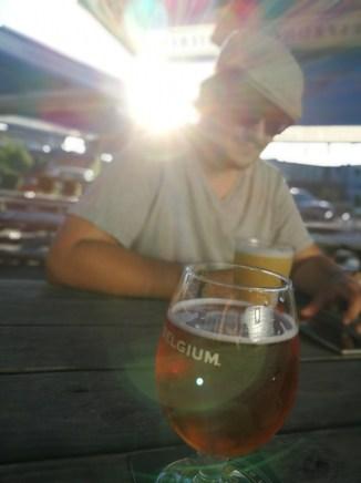 im Vordergrund ein Bierglas, im Hintergrund ein Mann mit Sonnenbrille und Sonne im Nacken