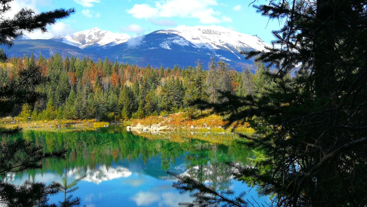 See mit schneebedeckten Bergen im Hintergrund, umringt von Wäldern