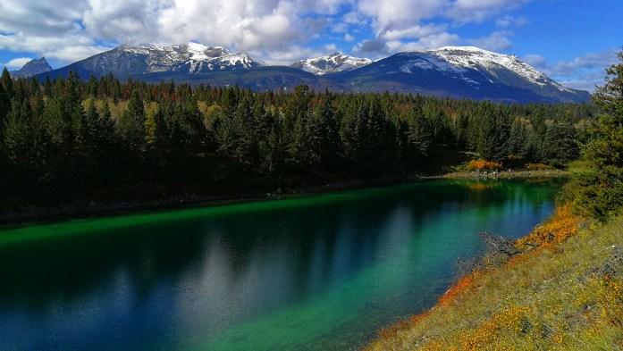 türkisblauer See im Tal der fünf Seen mit Bergen im Hintergrund und umringt von Bäumen