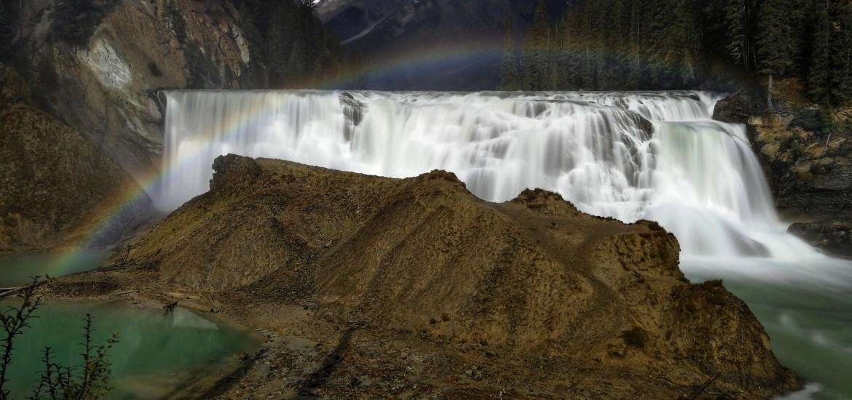 Ein Regenbogen spannt sich über einen Wasserfall