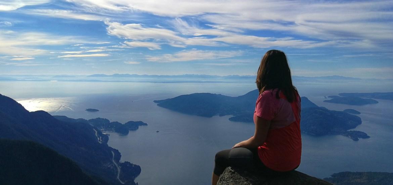 Person sitzt auf einem Felsen und blickt auf die Meeresbucht und Inseln