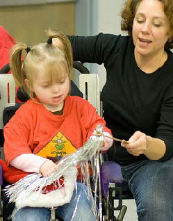 Young girl playing with a pom-pom along with her teacher.