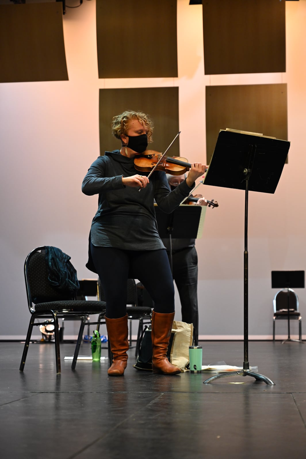 Martine is playing the violin, while standing and wearing a mask
