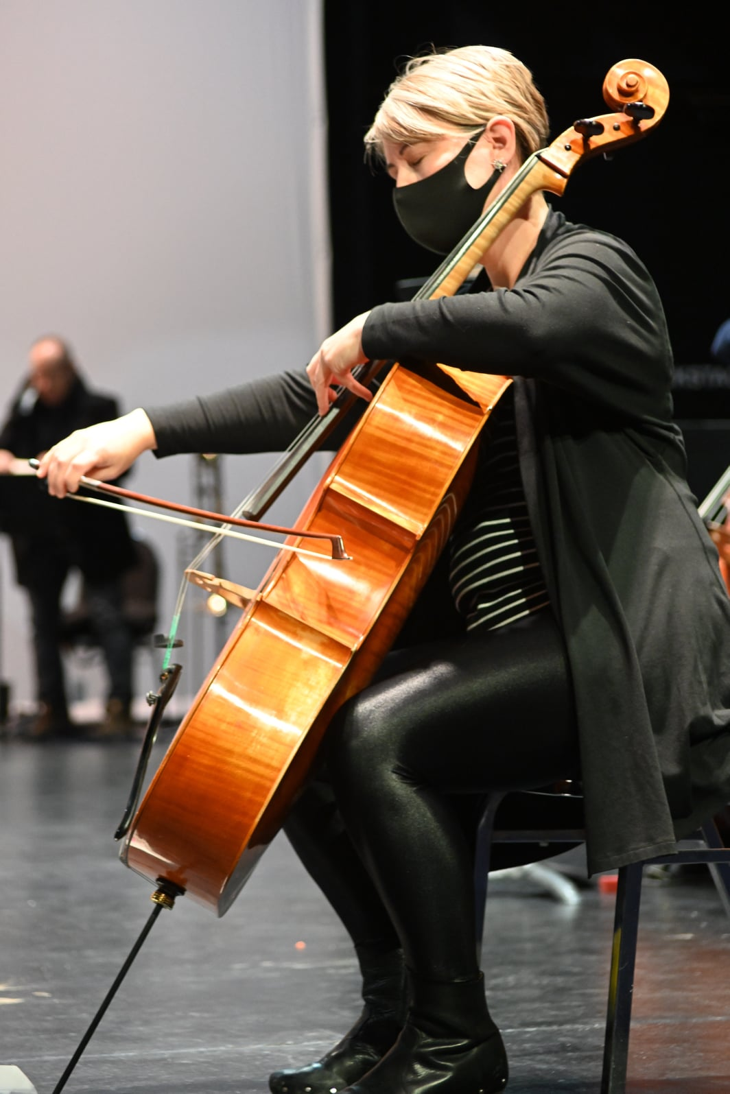 Olivia Walsh, wearing black and wearing a mask, playing the cello with her eyes closed