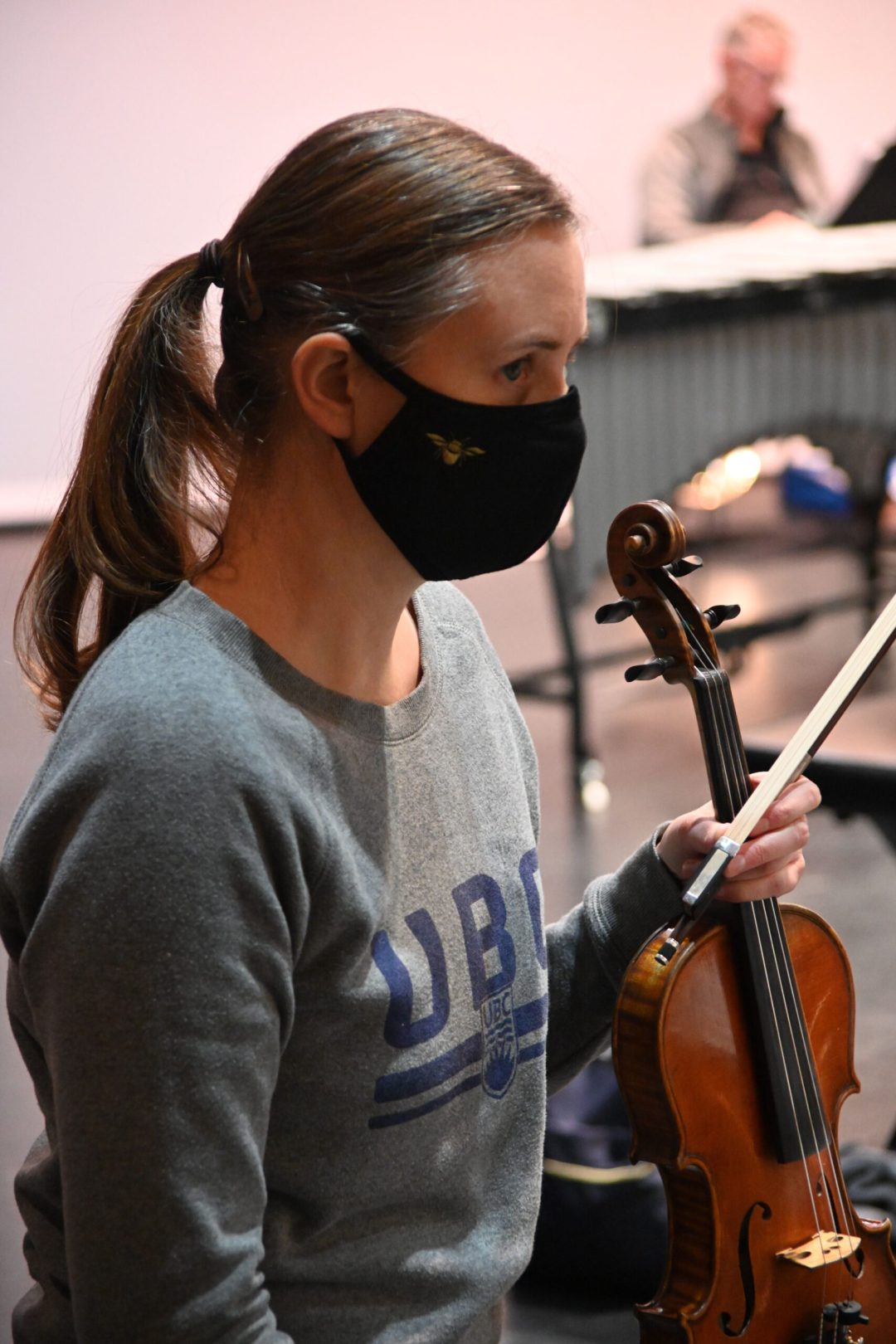 Sandra Wilmot in a mask, in rehearsal with her violin