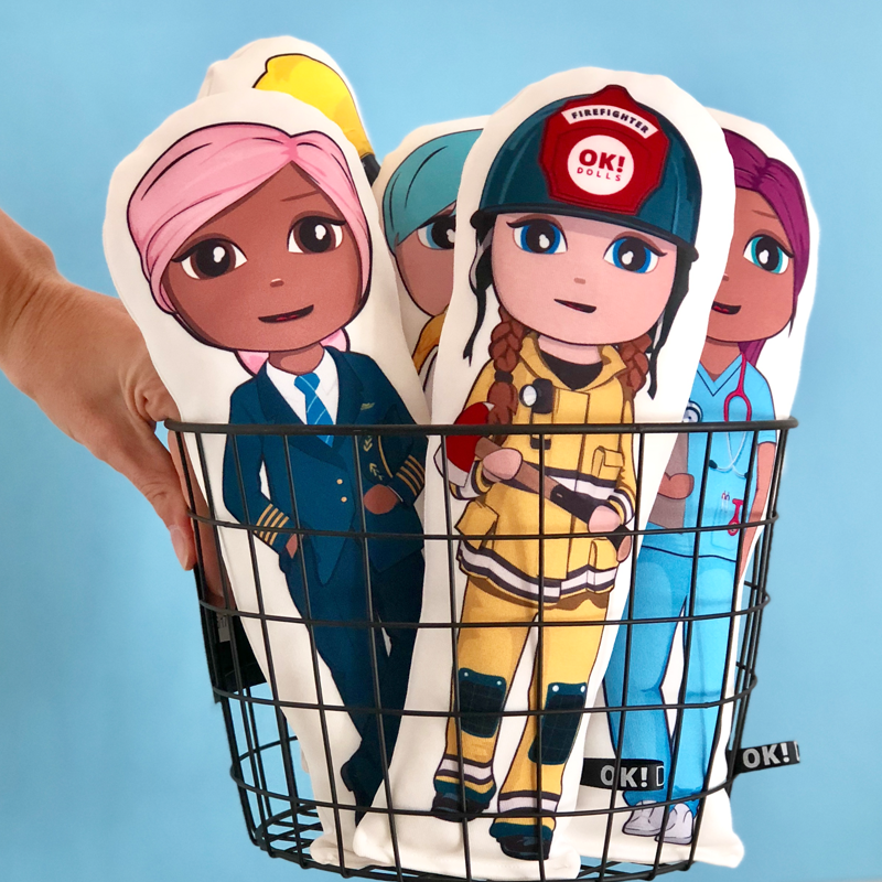 fire fighter doll and pilot doll in basket