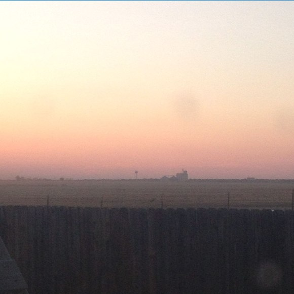Haze from wheat harvest hangs in the air with the local coop in the background.