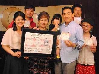CD制作に携わったメンバーら。発案した崎濱美和会長(前列左から2人目)、作曲の崎原永克署長(同4人目)、作詞の比嘉麻海さん(右端)