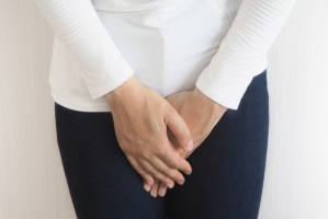 woman holding abdomen from fibroid pain