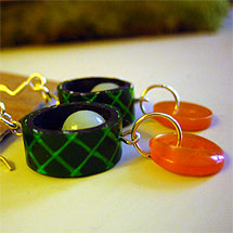 Örhängen av grönrutig plastslang och orange knappar