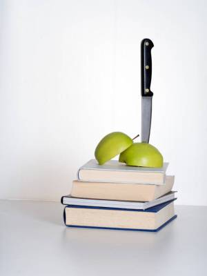 stack of books and apple stabbed by knife to represent education cuts