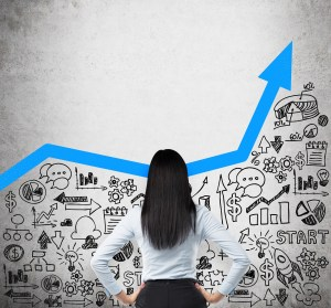 Rear view of the business lady who is looking for the new business ideas. Blue growing arrow as a concept of successful business. Business icons are drawn on the concrete wall.