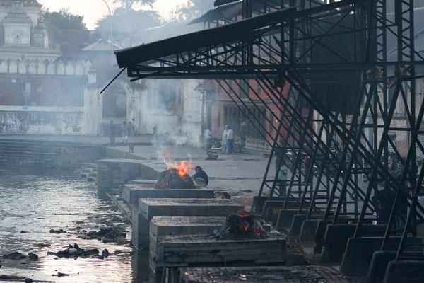 Kathmandu: sulle rive del  Bagmati, che attraversa il quartiere induista di Pashupatinat, si consuma un rituale funerale induista, con il cadavere che viene bruciato su una catasta di legna prima di venire trasportato nel  suo ultimo viaggio dalle acque del fiume sacro.