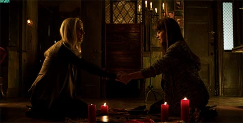 Lauren and Kenzi say incantations over a ouija board.