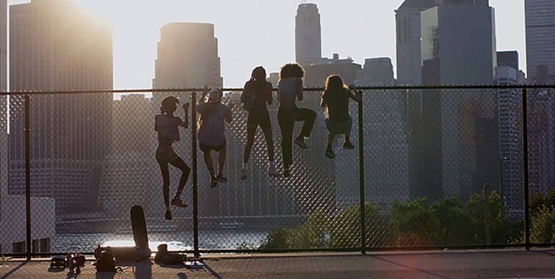 the cast of Skate Kitchen climb a fence