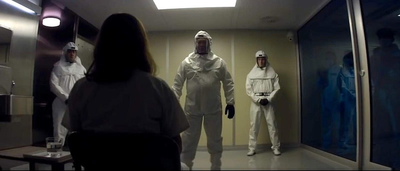Lena in an isolation chamber with men in protective suits.