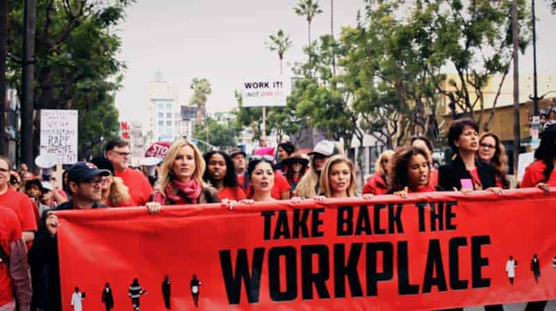 "Women marching with ""Take Back the Workplace"" on a banner"