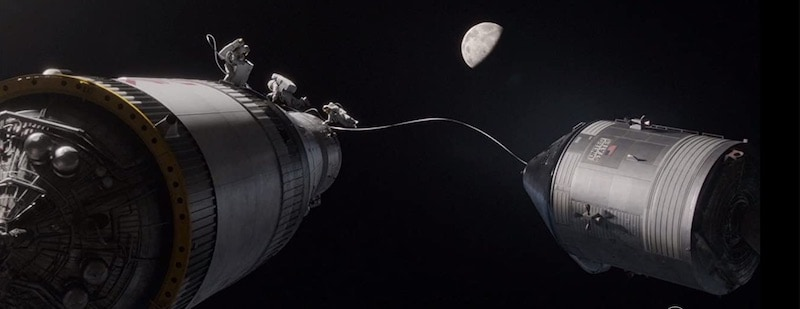 A scene in space with two tethered space ships against a backdrop of earth in the distance