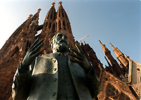 A statue of Antonio Gaudi y Cornet in front of his Sagrada Familia Cathedral.