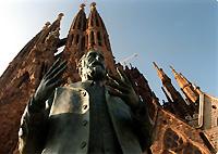 A statue of Antonio Gaudi y Cornet in front of his Sagrada Familia Cathedral.