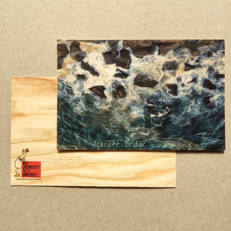 The image shows water smashing up against dark rocks. It was taken from above