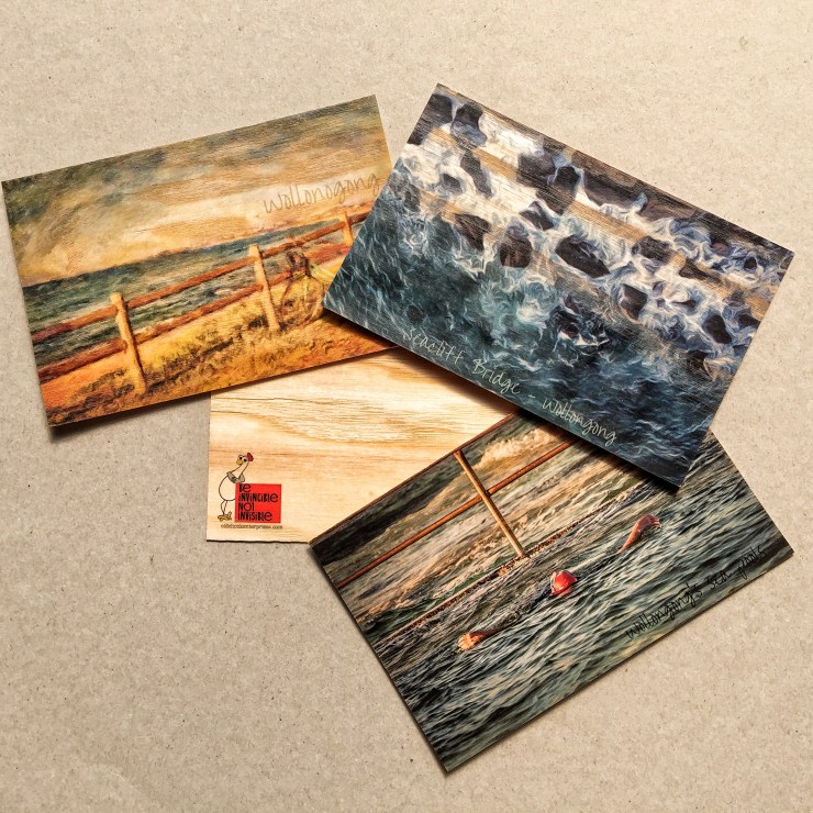 three wooden postcards showing scences of water and beach in the city of Wollongong, NSW, Australia.