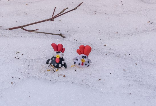 two small plastic chickens sit in snow