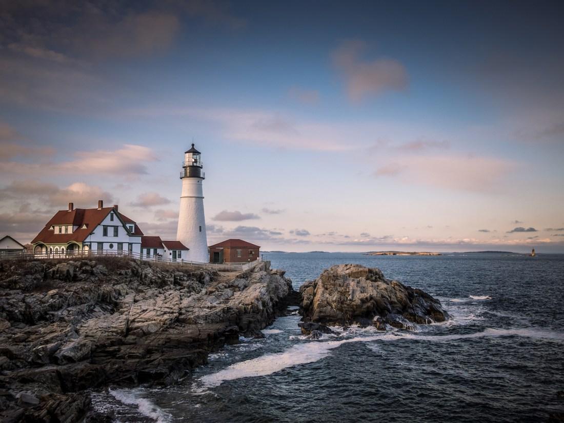a white lighthouse on a stony headland with pink sky