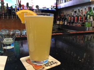 a glass of cloudy pale ale with a slie of orange sitting on a bar