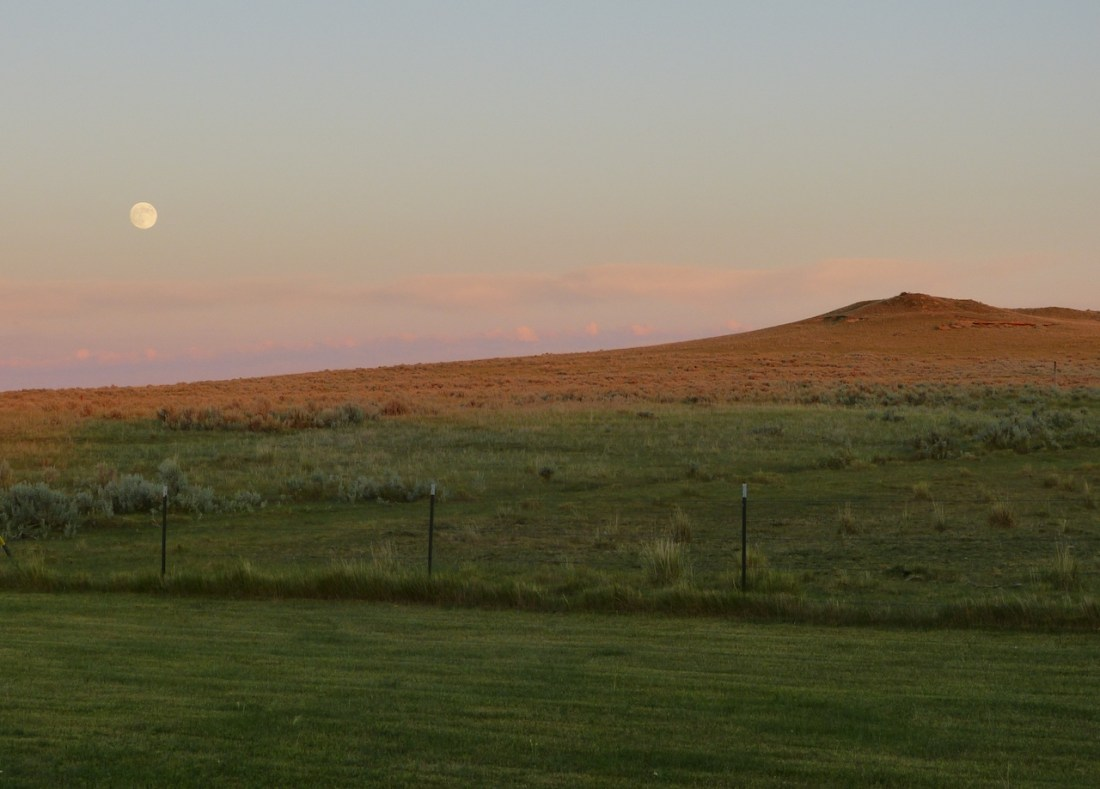 A grren grassy hill in the forwground and a red hill with teh moon rising in the the left hand side.
