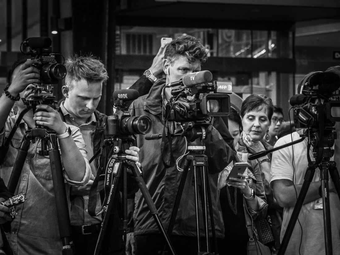 a group of photogepahers and one women reading another persons phone screen.