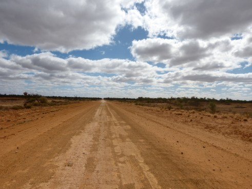 a red dirt road stretching into the horizon