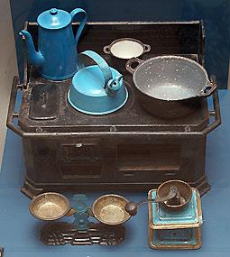 Dukkekomfur i jern fra Morsø Jernstøberi (bemærk at ovnlågen mangler) samt diverse køkkenudstyr. Komfur m.m. er fra ca. 1900 og fra Roskilde Museum