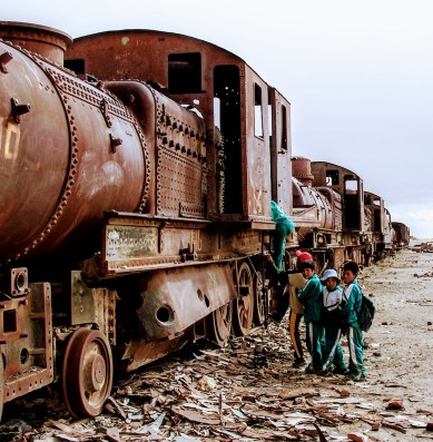 Children play on a rusty locomotive at Bolivia's train graveyard.