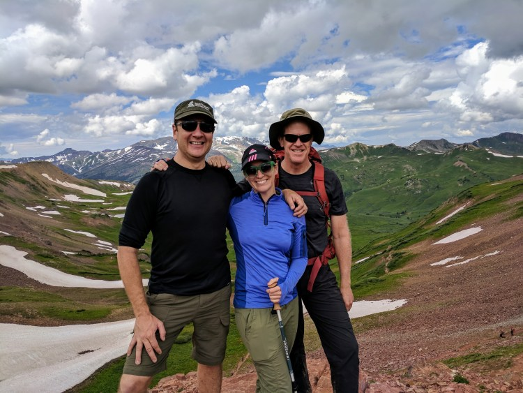 Three people at the top of West Maroon Pass