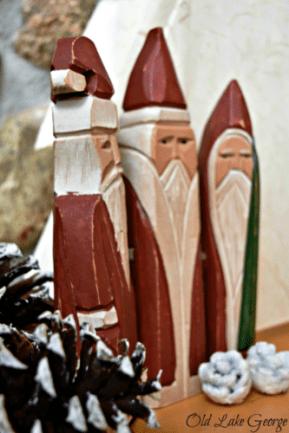Three wooden Santas on the mantle