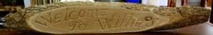 sign carved on a bark edged slab of wood