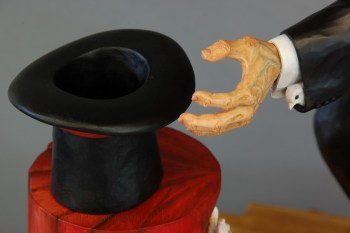 The head of a dove peeks out of the left hand sleeve of the Magician's coat.