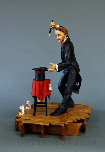 Dylan Goodson's wood carving of a magician standing on stage with wand upraised, about to conjure something out of the hat sitting on the table in front of him.