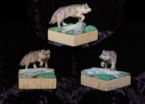 Two inch square wood carving of a wolf stepping over a log