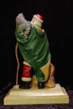 Santa Claus with a raccoon on his shoulder holding a walking stick carved by dylan goodson back view