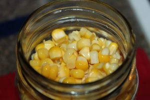Cold pack corn in hot mason jars, leaving 1 inch head space