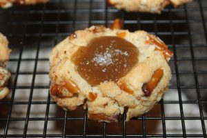 Pretzel cookie sits on the cooling rack filled with caramel