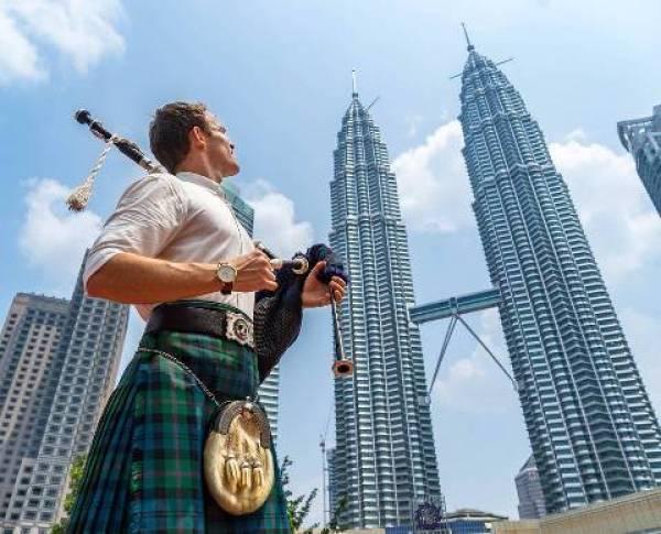 Escocês com gaita de fole em frente Petronas Twin Towers na Malásia