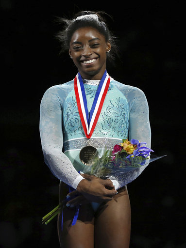 Simone Biles in her teal leotard, supporting the victims of Larry Nassar, with her gold medal and commemorative flowers.