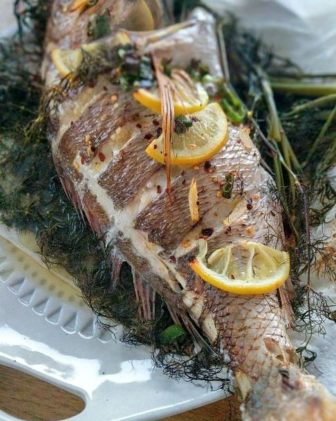Whole Snapper Baked Mediterranean Style on a bed of herbs