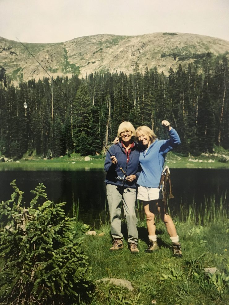 Two women stand proudly by mountain lake